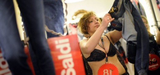Woman looks at a pair of pants at a Desigual store on the first day of winter sales in downtown Turin