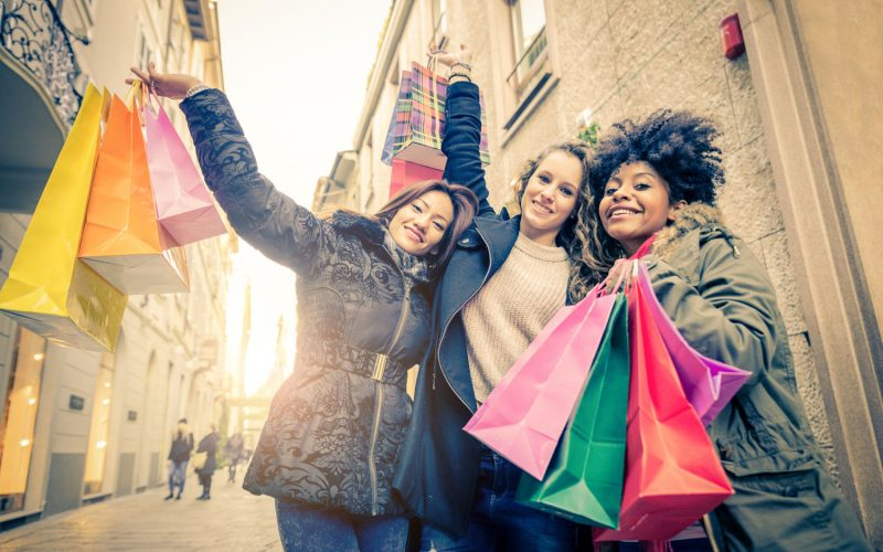 Women with shopping bags - Portrait of three pretty girls walking and looking at shops - Tourists buying clothes and presents