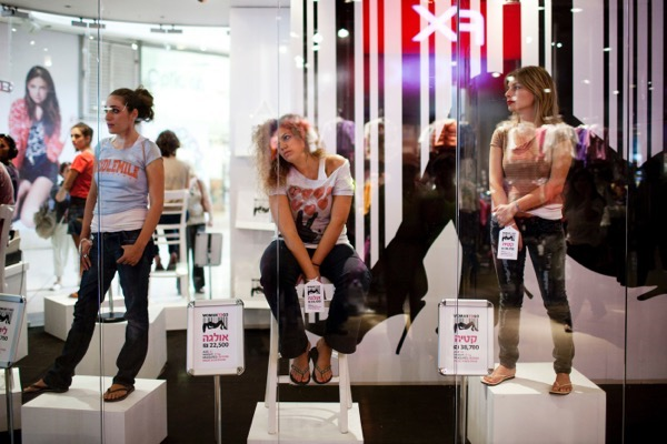 TEL AVIV, ISRAEL - OCTOBER 19: (ISRAEL OUT) Women stand in a store window at a shopping mall with price tags on their hands on October 19, 2010 in Tel Aviv, Israel. The store, opened for a day, was used to raise awareness of the trafficking of women. (Photo by Uriel Sinai/Getty Images)